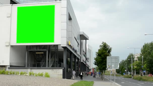 Billboard on a building (shopping center) - green screen - street with people and road (cars) - cloudy sky with nature (trees)