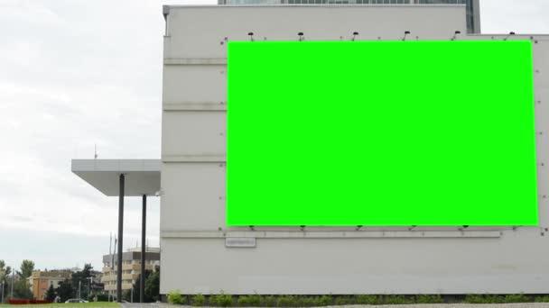 billboard na budovu (obchodní centrum) - zelené obrazovky - s lidmi v pozadí - zamračená obloha - budovy s přírodou v pozadí
