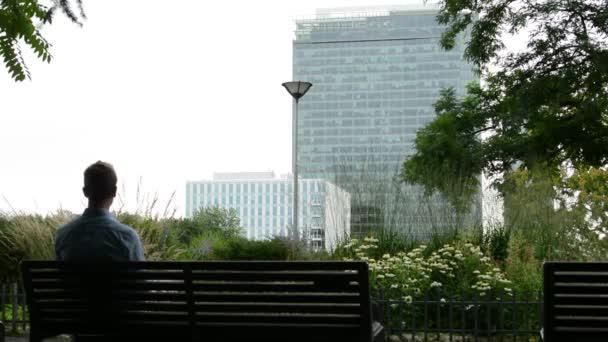 mladý muž sedí v parku - (přírody - stromy, květiny, keřů) na lavici