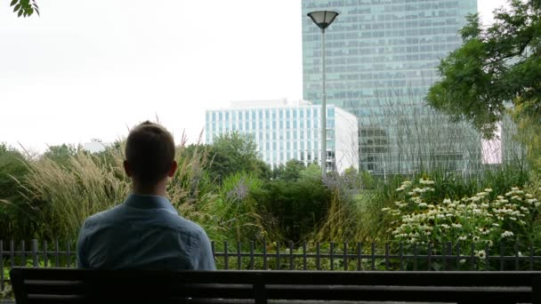 mladý muž sedí v parku - na lavičce - man telefonů a pak listy
