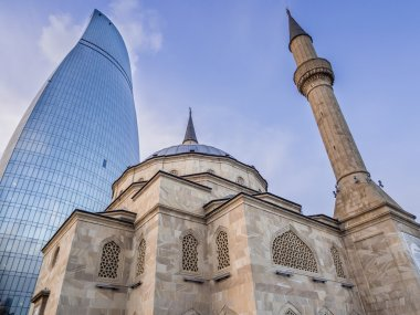 BAKU, AZERBAIJAN - NOVEMBER 22, 2013: Sehidler Mescidi Mosque next to the Flame Towers in Baku, Azerbaijan. Flame Towers are the first flame-shaped skyscrapers in the world.