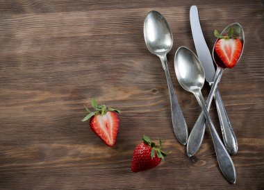 Vintage silverware on brown table with strawberry country style