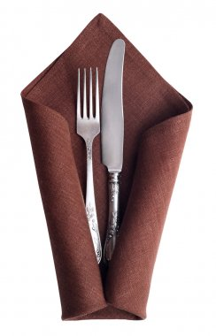 Vintage knife and fork at napkin isolated on white background.