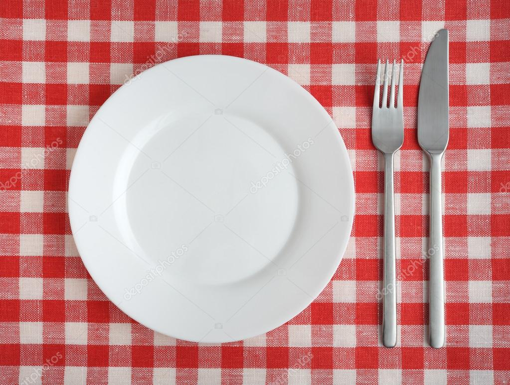 Plate with fork and knife on a red checkered tablecloth. \u2014 Stock Photo & Plate with fork and knife on a red checkered tablecloth. \u2014 Stock ...