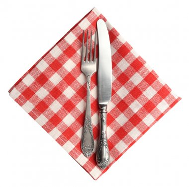 Vintage knife and fork on red plaid linen napkin isolated on white background.