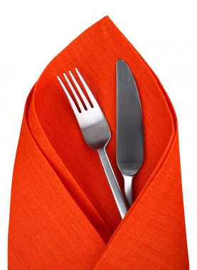 Orange napkin with knife and fork isolated.