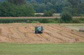 fotografie traktoru s přívěsem plné balíků sena