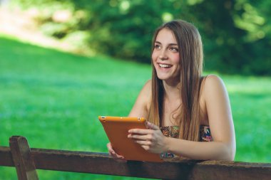 Beautiful young woman sitting on the bench in park with tablet