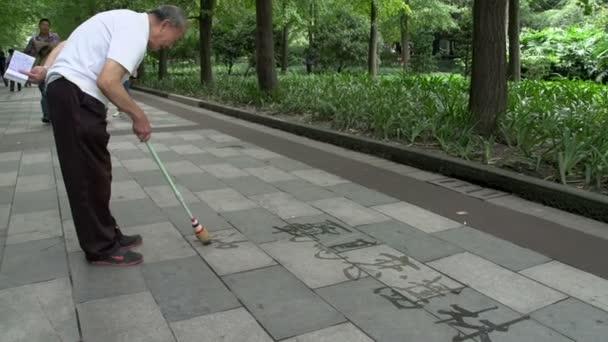 starší muž calligraphing čínské znaky s vodou