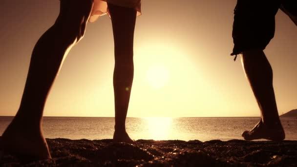 pár běží směrem k moři při západu slunce