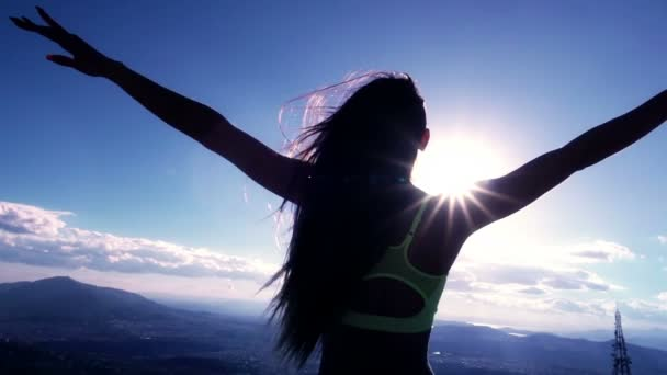 Silhouetted woman at the mountaintop