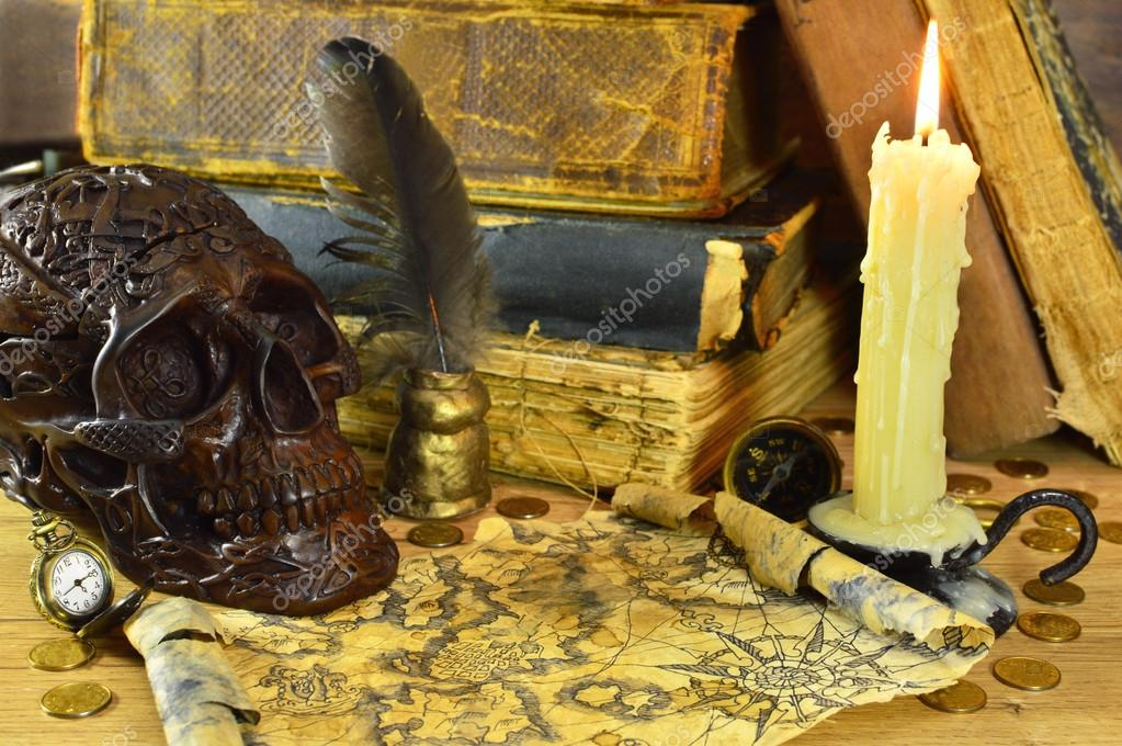 Skull with burning candle, pirate map and old books — Stock Photo