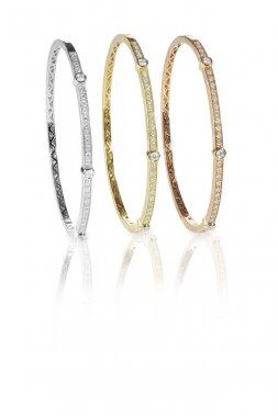 Set of three colored gold diamond bangle bracelets standing upri