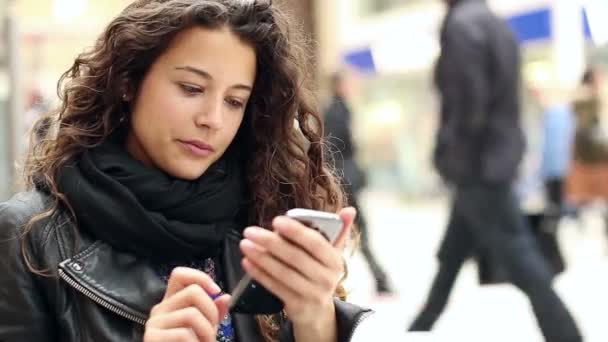 Attractive young woman using her touch screen phone