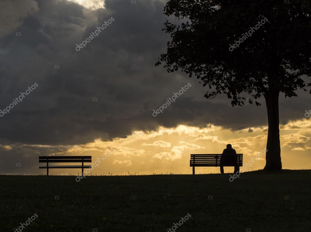 Anonymous silhouette man sadly sits on a bench alone during a dark cloudy sunset