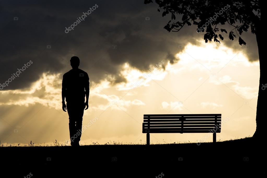 Silhouette of an anonymous man walking against a backdrop of dark clouds with sunlight breaking through