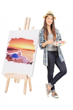 Female artist leaning on an easel with painting