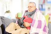 Fotografia uomo malato sul divano, bere tè caldo