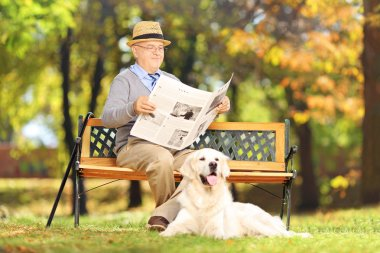 Senior man reading a newspaper with dog