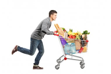 Young man running and pushing a shopping cart full with food isolated on white background stock vector