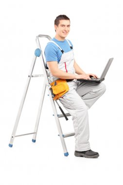 Man with laptop on ladder