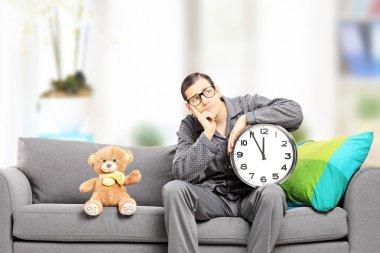 Man in pajamas holding a clock