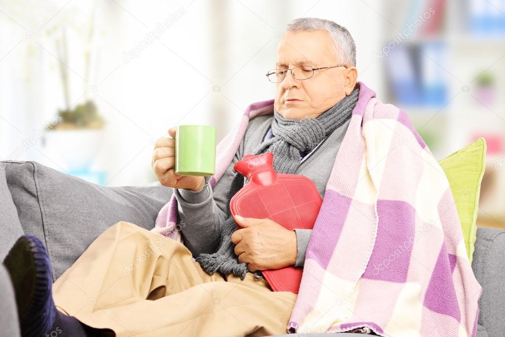 Ill man on sofa drinking hot tea
