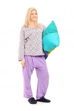 Blond girl in pajamas holding pillow