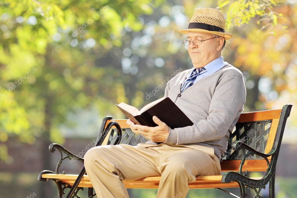 Senior man reading a book in park