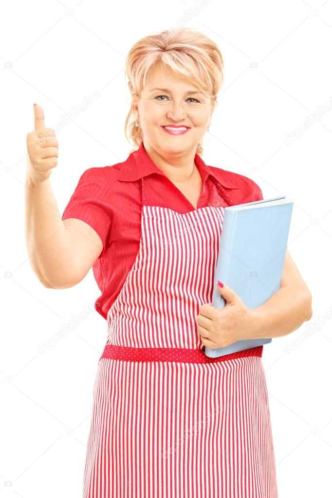 Smiling mature female cooker with apron holding a cookbook and giving thumb up isolated on white background