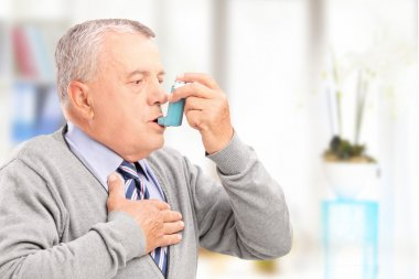 Man treating asthma with inhaler