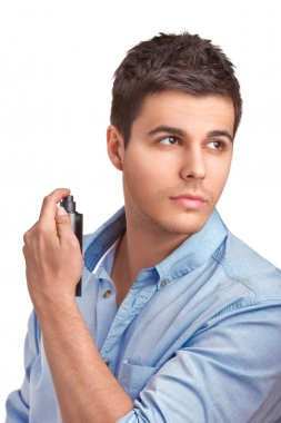 Handsome man using perfume