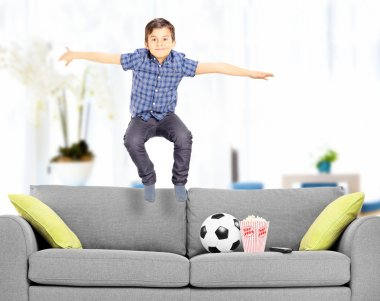 Overjoyed boy jumping on couch at home