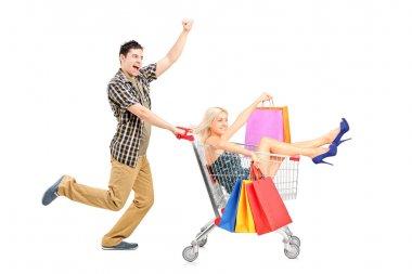Person pushing woman in shopping cart