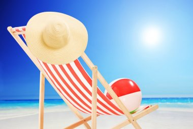 Beach chair with ball and hat on a sunny day by the sea stock vector