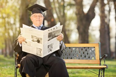 College professor reading newspaper in park