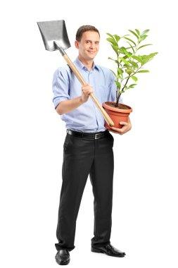 Man holding plant and shovel
