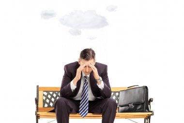 Stressed businessman sitting on bench