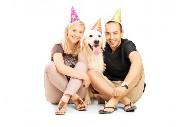 Couple with dog seated on floor