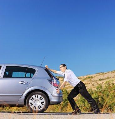 Businessman pushing car