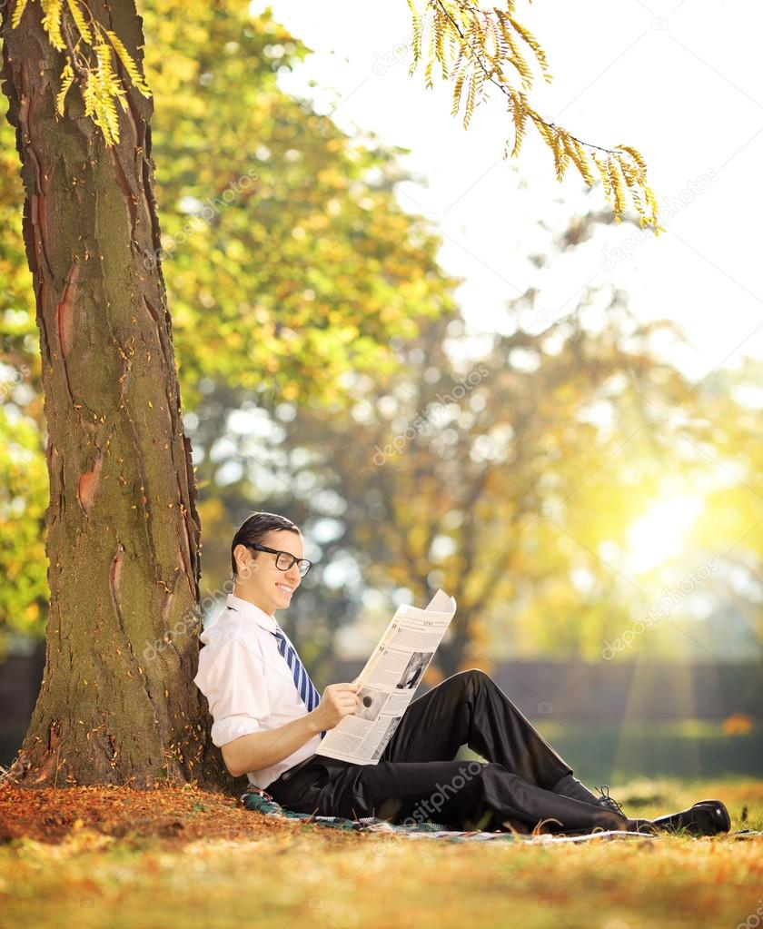Man reading newspaper in a park