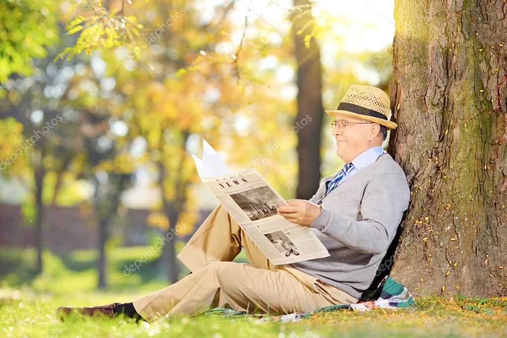 Senior reading a newspaper in a park