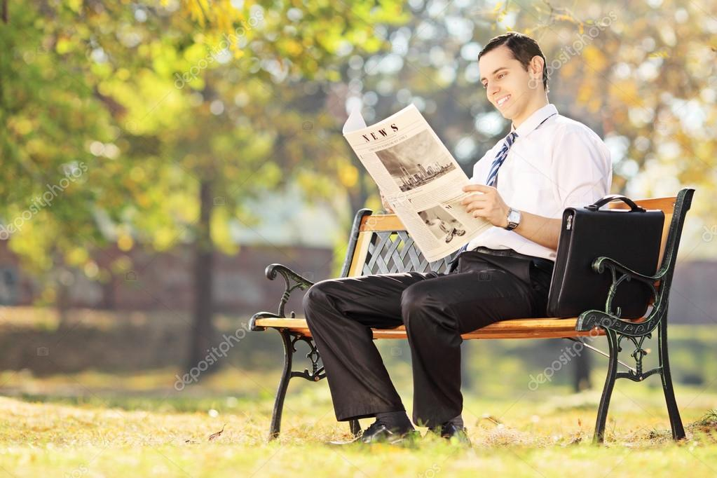 Man reading a newspaper in park