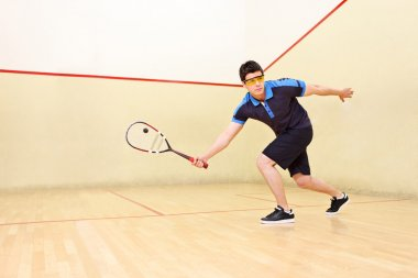 Squash player hiting ball