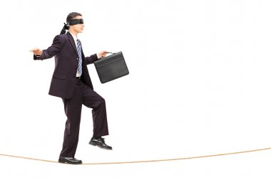 Businessman walking on rope