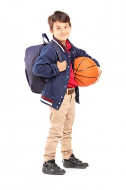 Schoolboy with backpack holding basketball