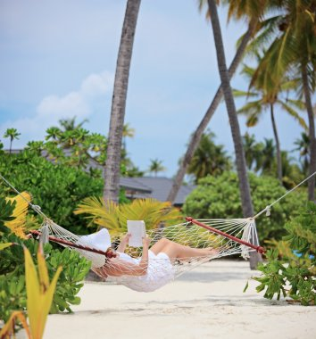 Woman relaxing in a hammock and reading