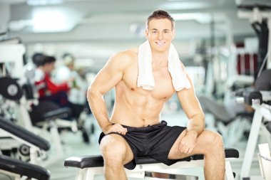 Muscular guy sitting in gym