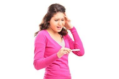 Worried female checking pregnancy test
