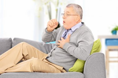 Man coughing seated on sofa